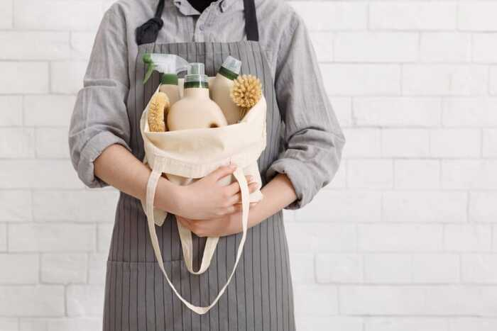 cleaning supplies person with a grey apron and a grey shirt holding a white bag with cleaning supplies