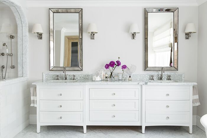 modern white bathroom with two silver framed mirrors and white furniture