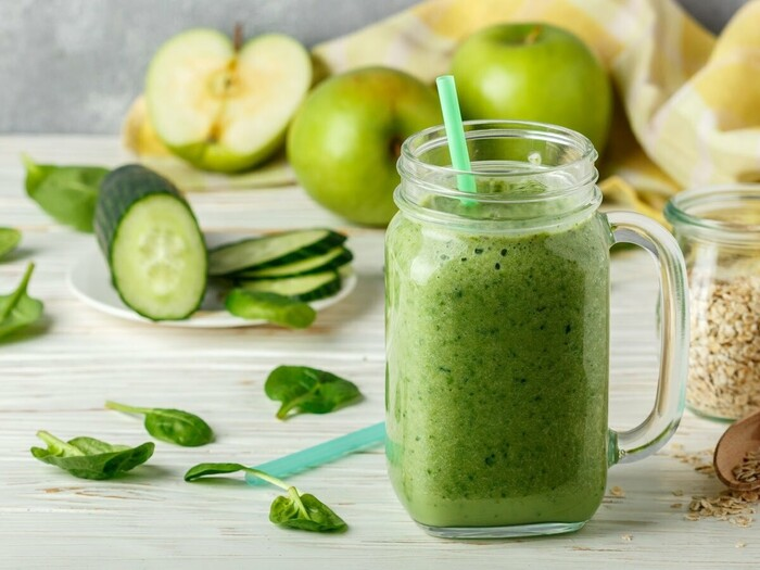 cucumber juice in a glass jar with a green straw on a white table with green apples cucumbers and mind leaves