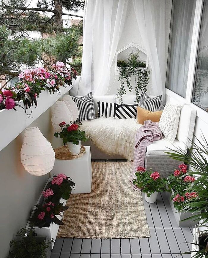 cute small urban balcony with living flowers lanterns and a seating area grey tiled floor