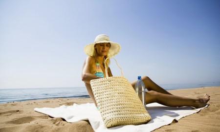 Young woman on beach, wearing sunhat