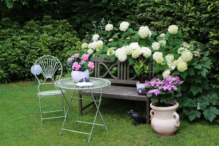 cute garden spot with a table chair and a bench with flowers all around