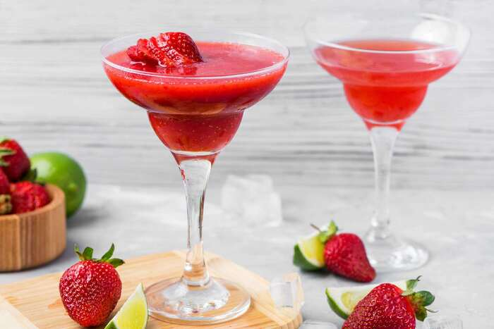 red daiquiri in tall glasses decorated with strawberries and other fruit