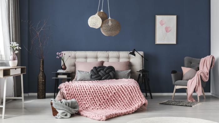 Statement decor pieces pink knit blanket modern light fixture and dark blue wall