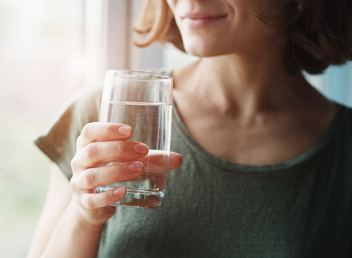 woman in a green shirt with short hair holding a glass of water looking through the window