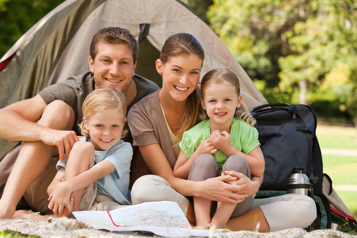 family camping family of four in front of a tent in a park