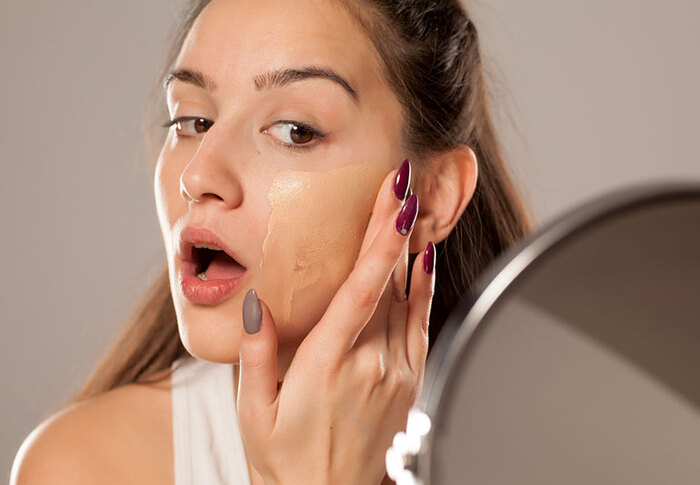 woman applying foundation on her face looking in the mirror