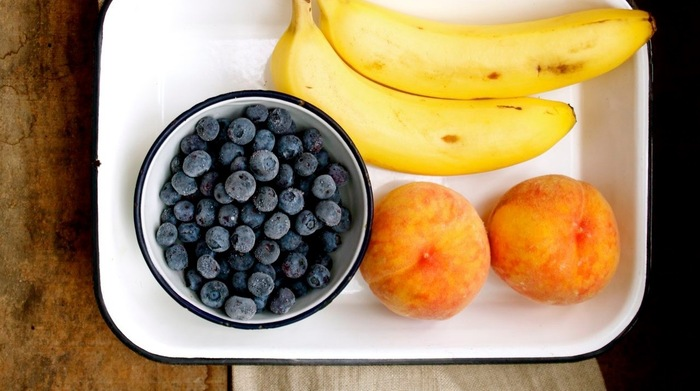 fruit serving blueberries peaches and bananas on a white tray on a wooden table