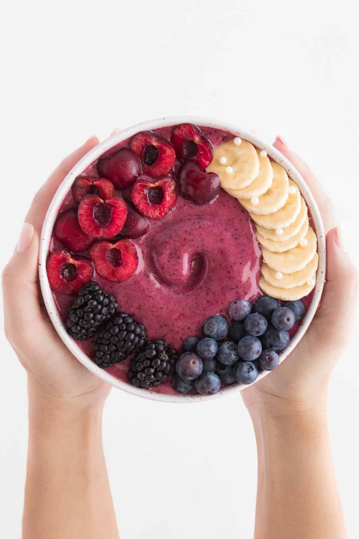 fruit smoothie ball best foods for health two hands holding a smoothie bowl with different berries cherries and bananas