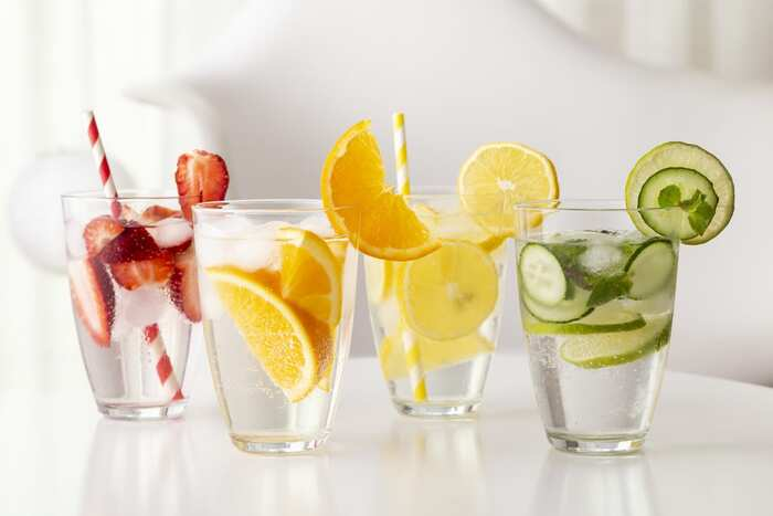 glasses with infused fruit water with cucumber strawberries orange lemon and colorful straws
