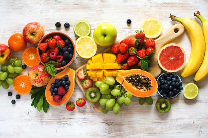 different fruits arranged on a white wooden table tropical fruits grapes bananas papaya limes and other fruits