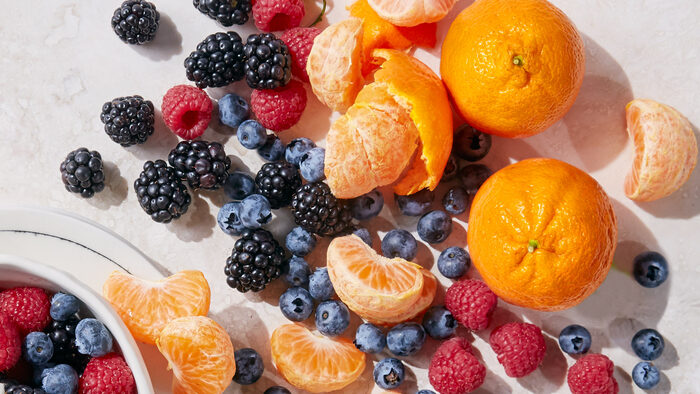 fruits on a table blueberries blackberries and tangerines spread on a table