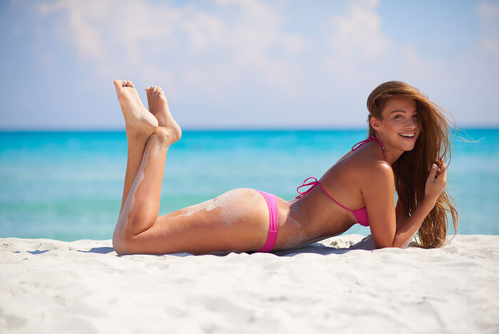 girl in swimsuit lying on the beach in pink swimsuit smiling and smiling at the camera