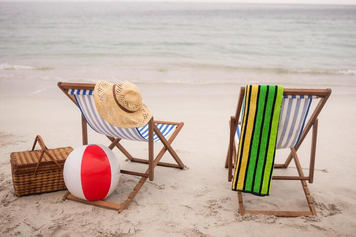 going to the beach two chairs with a towel sun hat beach ball and a basket