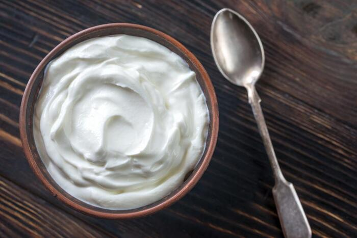 energy foods greek yoghurt in a brown bowl on a wooden table with a spoon next to it