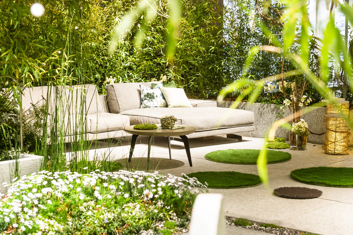 modern garden relax area with a light sofa bamboo and other greenery