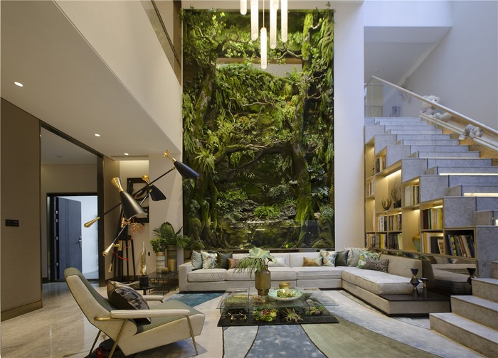 green living room design with a tall green living wall white staircase and modern furniture