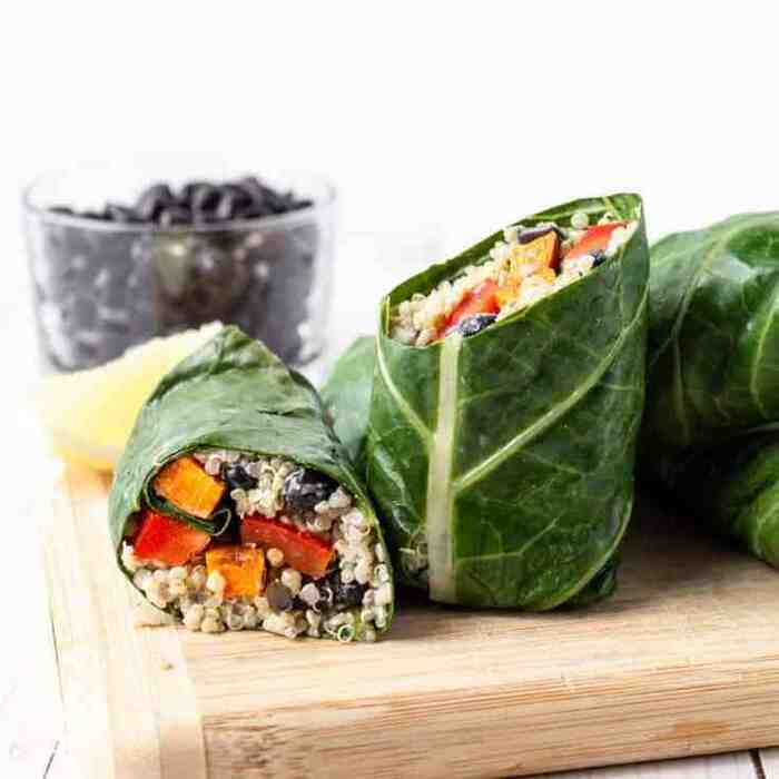 green wraps with a green leaf filled with veggies on a wooden board