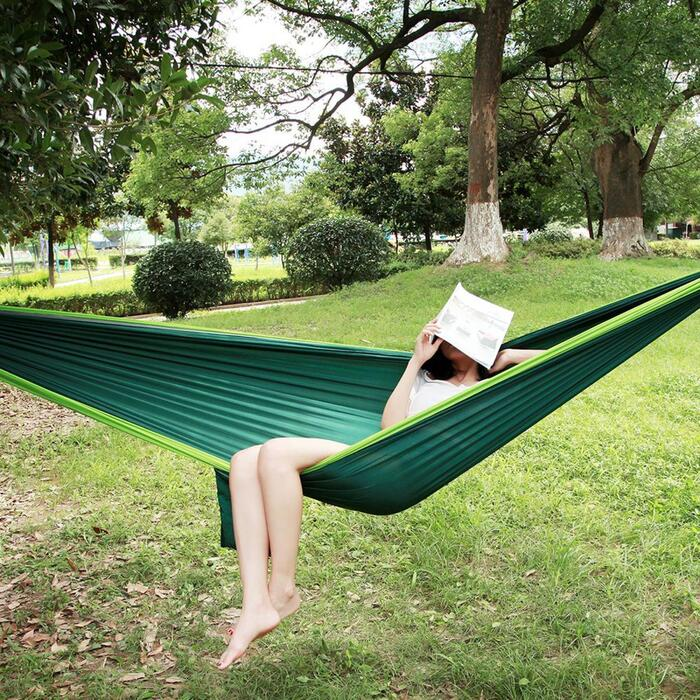 green hammock in a garden woman with a book on her face relaxing