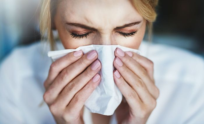 hay fever sneezing woman with a white tissue in front of her nose sneezing in it