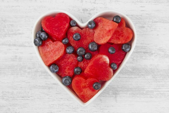 heart shaped bowl on a white table with hearts cut of watermelon and blueberries