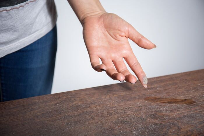 home dust woman in jeans checking the dust on a wooden surface with her fingers