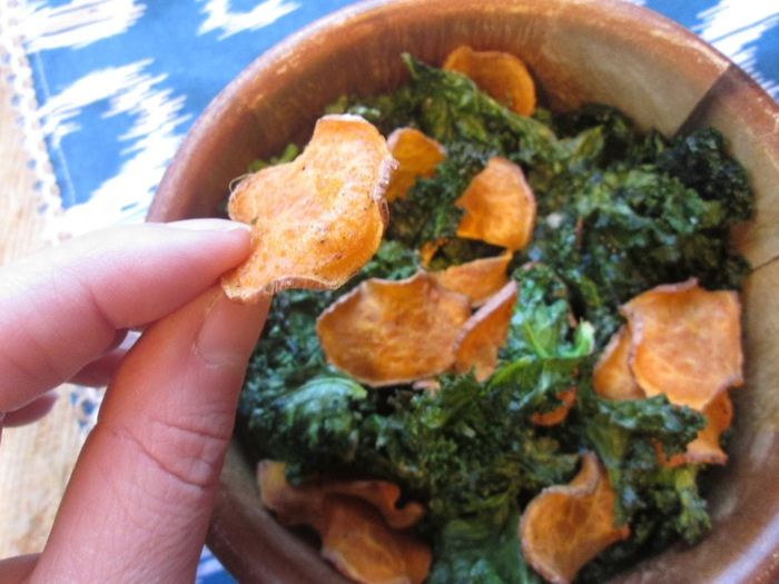 kale and sweet potato chips in a wooden bowl woman holding a piece