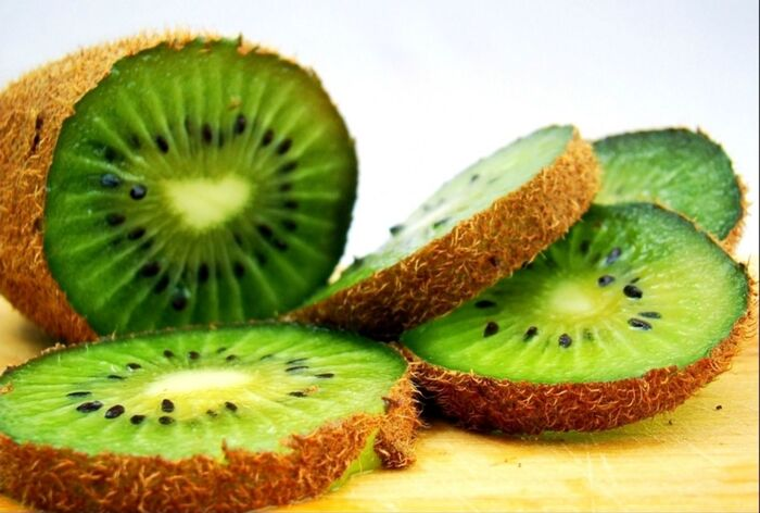 kiwis sliced green kiwi on a table with light background