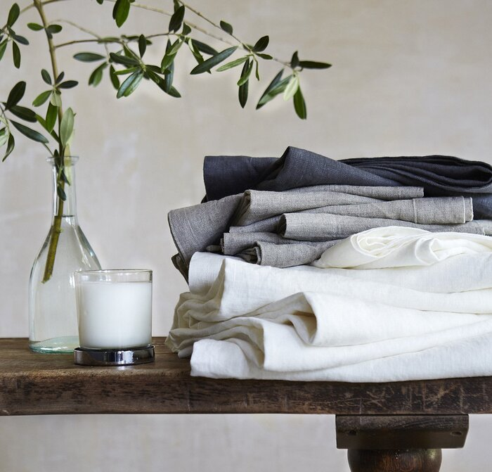 white and grey linen towels on a dark wooden table with a white candle and a branch in a vase