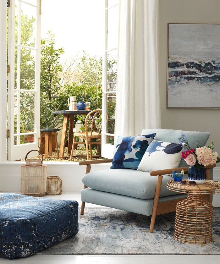 artistic living room with light blue accents decorative pillows painting on the wall and a terrace