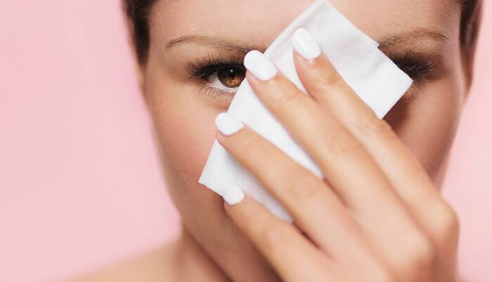 woman with white nail polish using a white wet wipe to take her makeup off