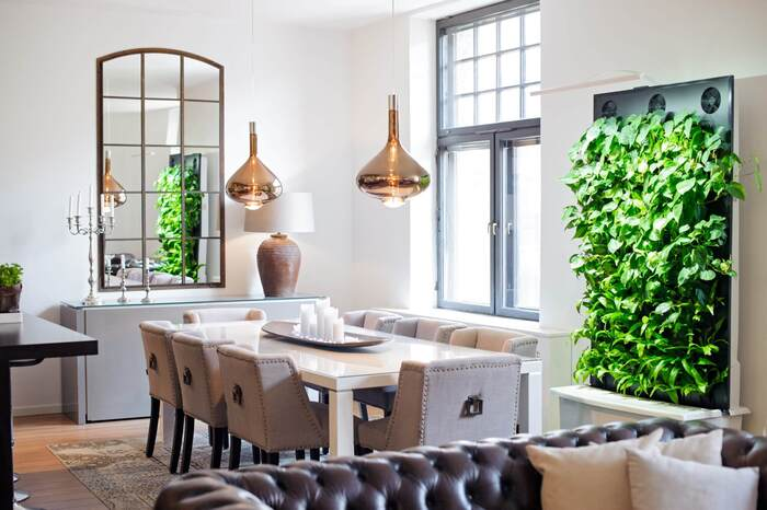 modern dining space with a green wall metallic lights and natural light