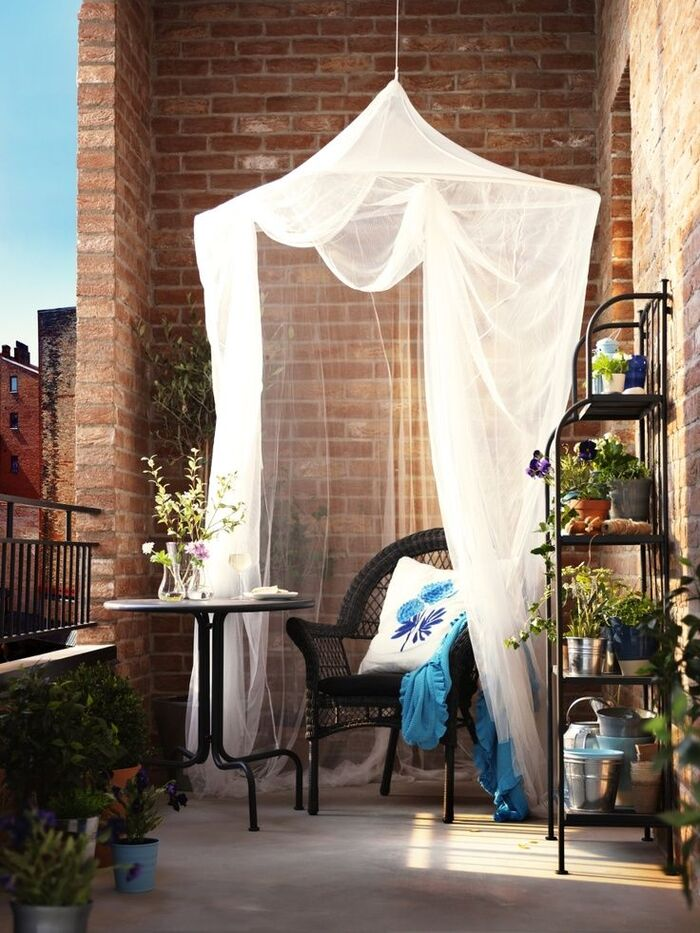 mosquito net in a small balcony over a chair and a small round table with brick walls around