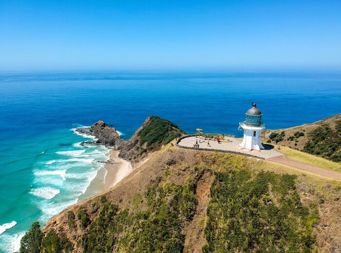 new zealand cape with a lighthouse overlooking the blue sea white waves crashing in the rocky shore