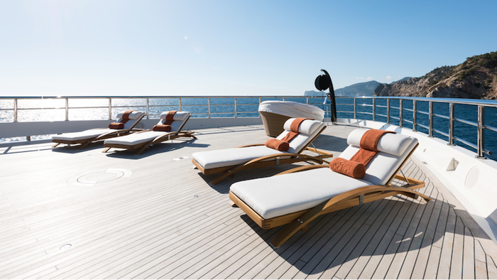 modern yacht deck with white lounge chairs and a rocky coast in the background