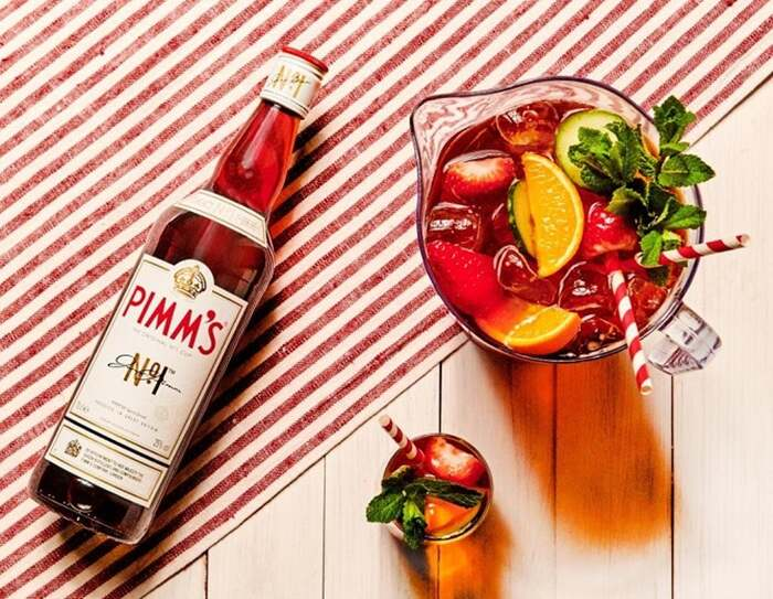pimms cup cocktail bottle of pimm and a huge jug filled with fruit ice and cocktail on a red and white table