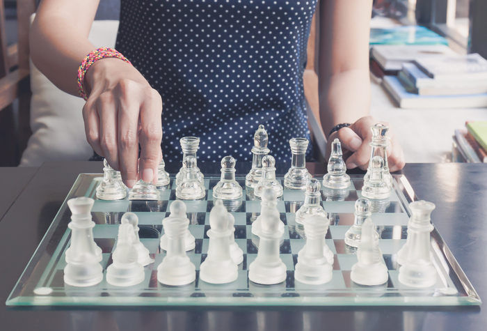 playing chess daily habits woman in a dark blue dotted dress playing chess with transparent figurines