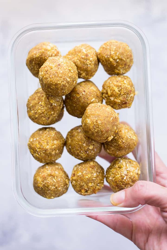 protein candy balls in a glass container woman holding it in her hand