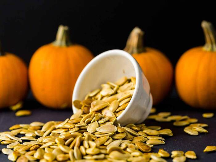 pumpkin seeds spilling from a white team cup with orange pumpkins in the background