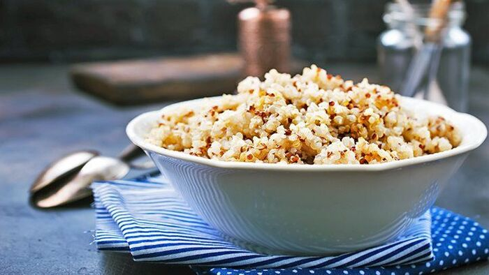 bowl with quinoa on a blue towel on a table with a spoon next to it and other kitchen ware in the background