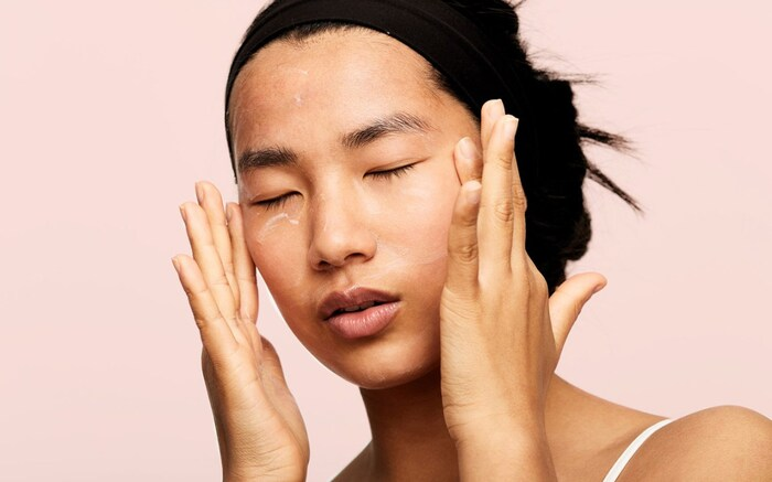 retinol face asian woman with her hair up applying cream on her face and under her eyes