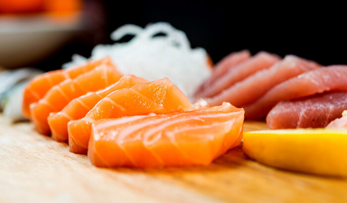salmon and tuna fish slices ion a wooden table with lemon