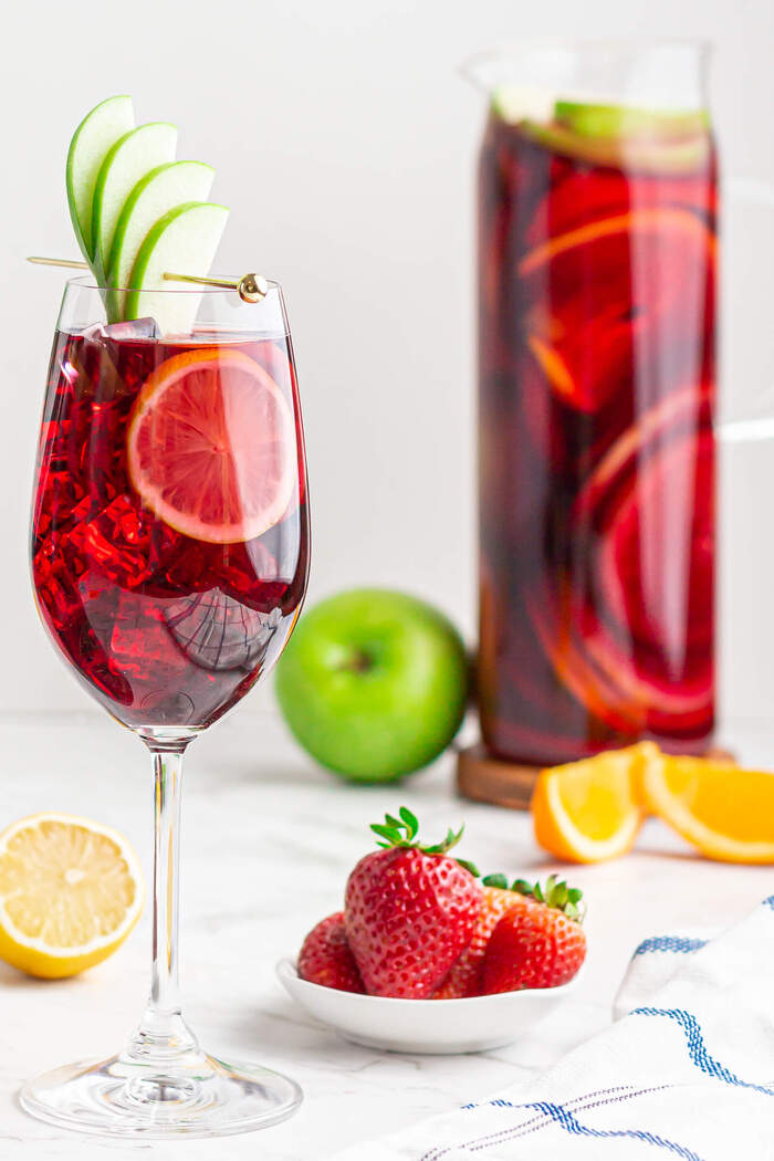 sangria in a glass with apple slices and different fruits