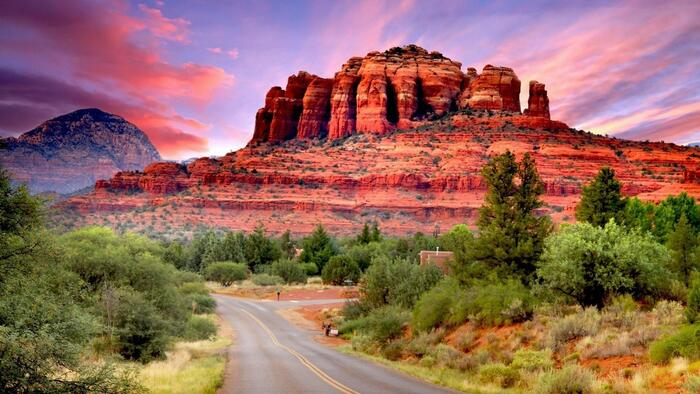 red mountains in sedona usa at sunset with low green trees around
