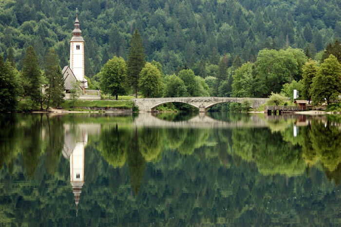 slovenia lake bohinj with a stone bridge and a white tower surrounded by forests