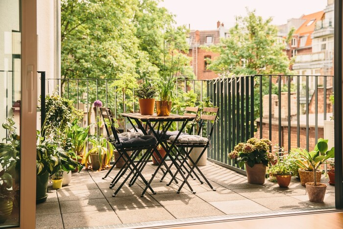 small balcony oasis in the city with living plants tiles on the floor and a small table with chairs