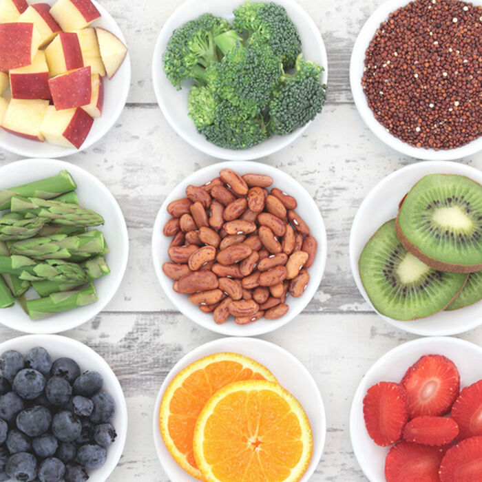 sources of vitamin A retinol different fruits vegetables nuts in bowls on a white wooden table