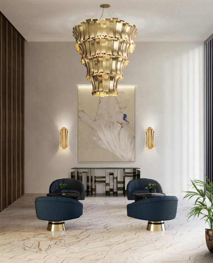 statement decor pieces large golden lighting fixture in a large living space with dark blue seating chairs