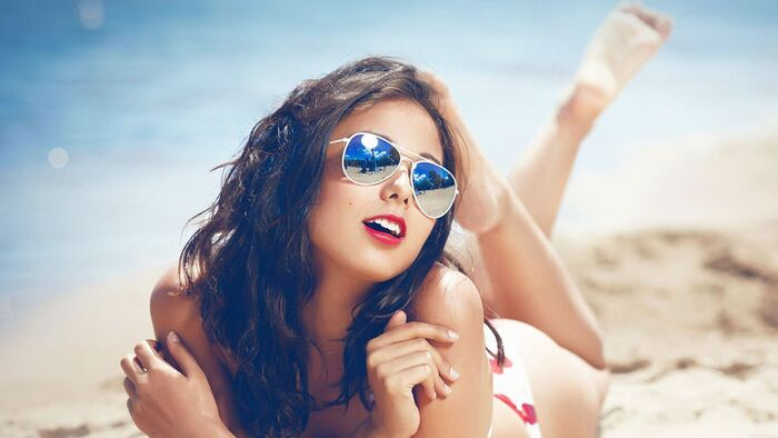 summer glasses woman lying on the beach with red lipstick and aviator sunglasses