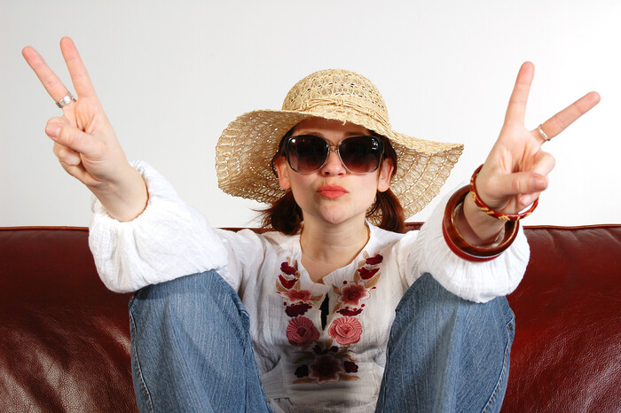 pandemic summer woman with a sun hat and sunglasses in jeans sitting on a coach with two hands up in a peace sign